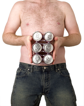 This image shows a young man holding a six pack of beer, over his belly.