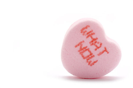 cynical: This image shows a candy heart with the phrease What Now on it. Stock Photo