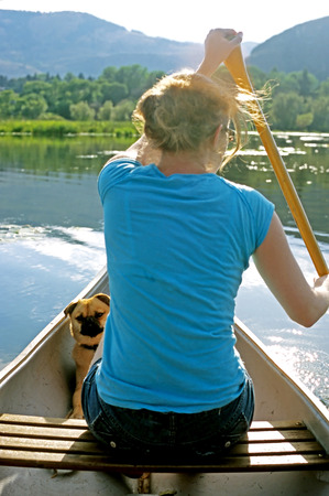 watchful: This image shows a watchful dog and her owner paddling a canoe on a calm lake. Stock Photo