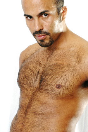 arm of a man: This image shows the torso of a muscular Hispanic man with trimmed chest hair.