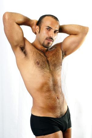 hombres sin camisa: Esta imagen muestra a un hombre hispano muscular con pelo en el pecho recortado en una pose sexualizada.