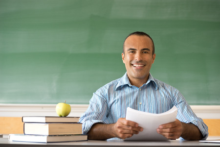 latin people: This image shows a Hispanic Male Teacher in his classroom