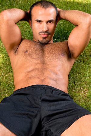 This image shows a sexy hispanic man doing Sit ups photo