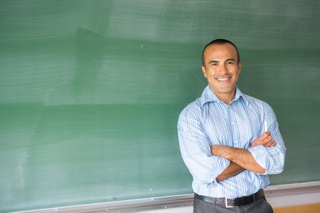 이 이미지는 자신의 교실에서 라틴 아메리카 인 남성 교사를 보여줍니다