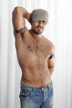 sin camisa: Esta imagen muestra a un hombre hispano muscular con pelo en el pecho recortado en una pose sexualizada.