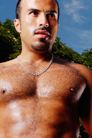 This image shows a muscular Hispanic male in a work out pose. photo