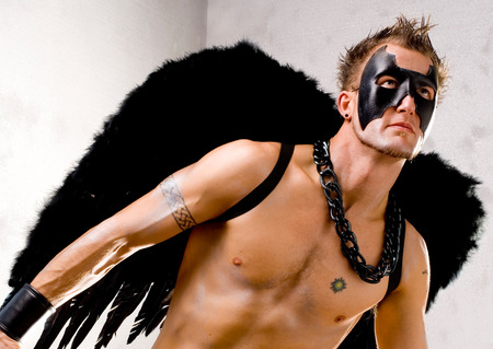 shirtless men: This image shows a fit guy wearing angel wings and a mask