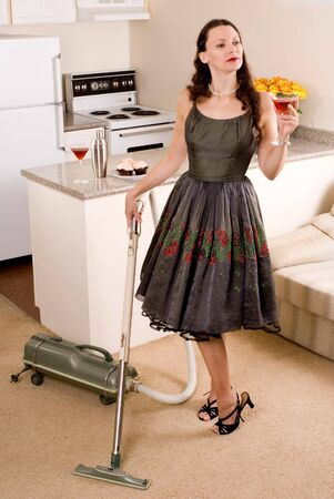 tempt: This image shows a vintage looking doing housework with cocktails in hand Stock Photo