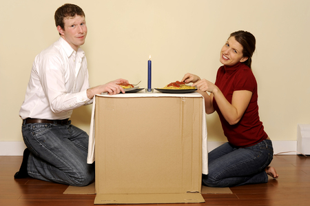couple lit: This image shows a couple on a budget having a candle lit dinner on their box table
