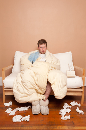 sniffles: This image shows a sick man on the couch
