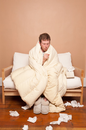 この画像は、ソファの上病気の人を示します。 写真素材