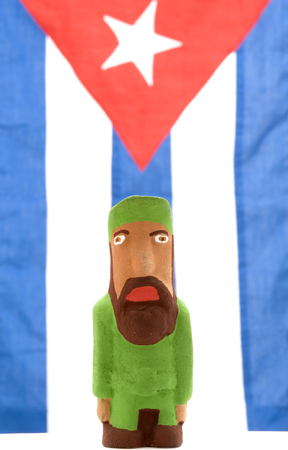 figurine: This image shows a Castro figurine against a Cuban flag