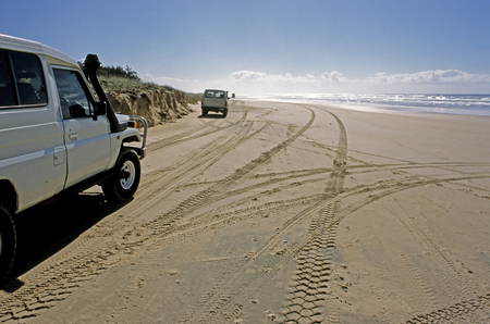 4wd: This image was shot on Australia's Fraser Island and shows a convoy of trucks making their way down the beach highway. Stock Photo
