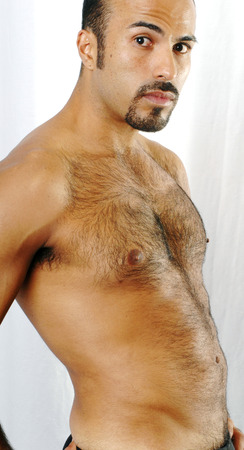 hairy arms: This image shows the torso of a muscular Hispanic man with trimmed chest hair.