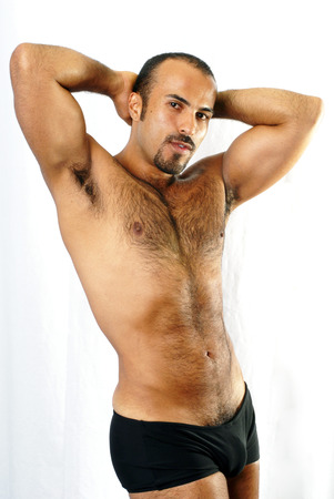 hairy arms: This image shows a muscular Hispanic man with trimmed chest hair in a sexualized pose.