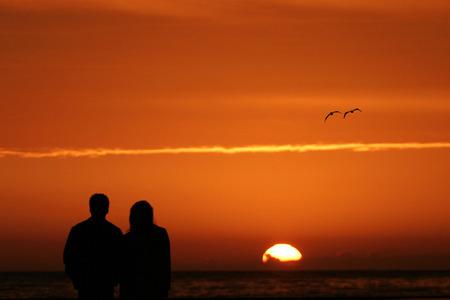 カップル、ビーチで夕日を眺め 写真素材