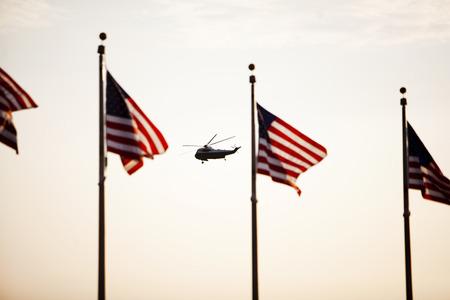 Silhouetted 워싱턴 기념비와 마린 하나의 헬리콥터