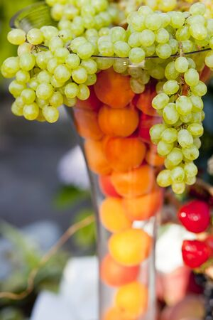 overflowing: Outside image of grapes overflowing out of a glass vase with oranges inside the vase