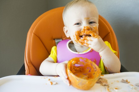 Messy toddler happy with food on face Stock Photo