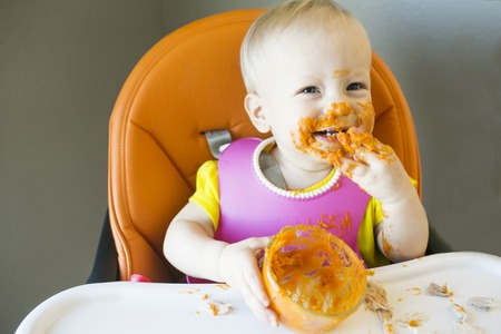 Messy toddler happy with food on face Stockfoto