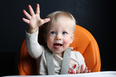 high chair: Happy toddler raising hand in high chair Stock Photo