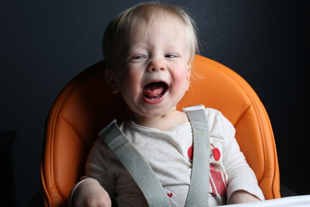 high chair: Happy toddler laughing in high chair