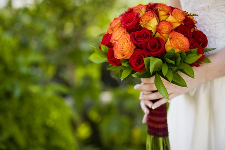 orange rose: Bride holding wedding bouquet of Roses and Ruscus flowers