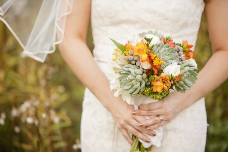hand holding flower: Bride holding wedding bouquet with Echeveria, Dahlia, Freesia, mini Hydrangea, Ranunculus, and Silver Brunia