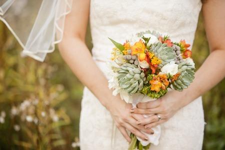 ranunculus: Bride holding wedding bouquet with Echeveria, Dahlia, Freesia, mini Hydrangea, Ranunculus, and Silver Brunia