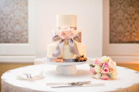 白いウエディング ケーキとバラ、ダスティ ミラー、ラナンキュラスの花束
