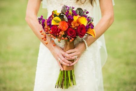 Braut mit Hochzeitsstrauß mit Hagebutten, Smokebush, und gelbe Calla-Lilien