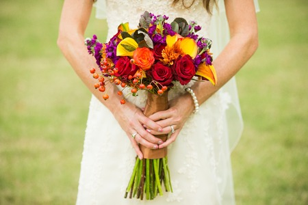 hand holding flower: Bride holding wedding bouquet with Rose Hips, Smokebush, and yellow Calla Lilies