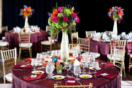 Mittelstücke der Rosen, Zierspargel, Delphinium, asiatischen Lilien, Wachsblume, Amaranthus, und springeri machte bei einer Hochzeitsfeier Standard-Bild