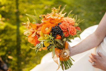 Braut mit Hochzeitsstrauß mit Rosen, Ranunkeln, Cymbidium Orchideen, Viburnum, Mokara Orchideen, und Mini Calla Blumen