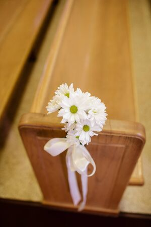 pew: Daisy decorations on a pew for a wedding ceremony
