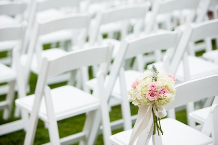 decor: Wedding ceremony decor consisting of Roses, Hydrangea, and Dusty Miller attached to the seats