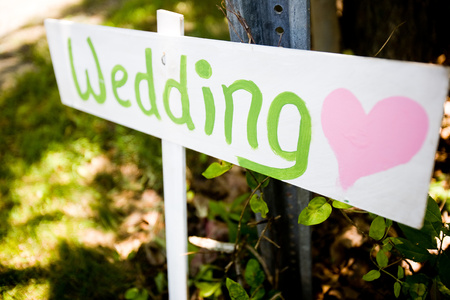 Wooden sign pointing towards a wedding ceremony