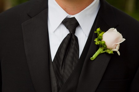 man in suit: Groom wearing a boutonniere consisting of a rose and hypericumat a wedding.
