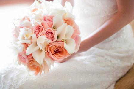 Bruid met mooie oranje en roze bruiloft boeket bloemen, bestaande uit witte mini calla lelies, rozen en witte orchidee.