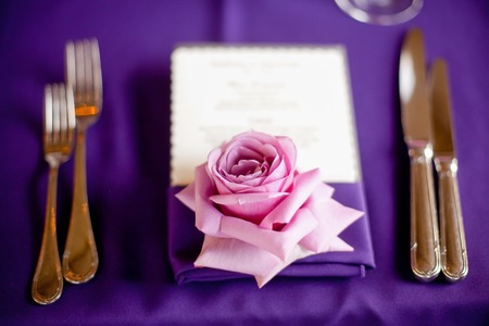Rose at a formal dinner against a purple table cloth