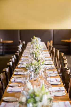 Long table in a restaurant set for an event such as a wedding reception or banquet