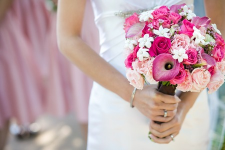Bride holding beautiful wedding bouquet consisting of light pink roses, hot pink roses, pink calla lilies, and stephanotis pink wax flower Stock Photo