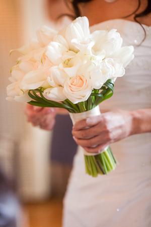 matrimonio feliz: Novia que sostiene el ramo hermoso de flores blancas que consta de tulipanes blancos, calas blancas, rosas marfil