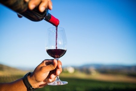 red wine pouring into glass Stock Photo