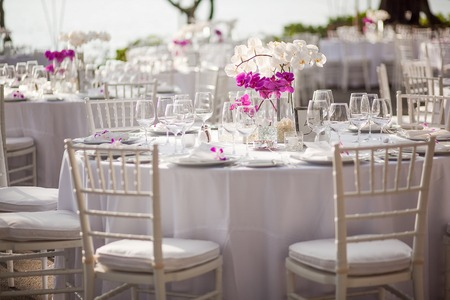 ao ar livre: peça central da orquídea em um evento ou recepção de casamento ao ar livre