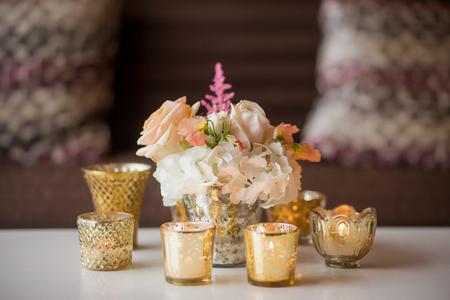 キャンドルに囲まれたテーブルの上の花の小さなアレンジメント