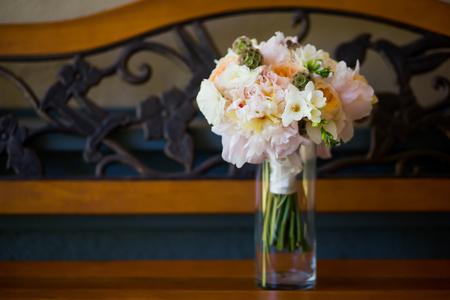 Blumenstrauß der hübschen Blumen in der Vase aus Rosen, Fresien, Craspedia auf einer Bank sitzt