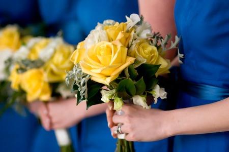 파란색 드레스를 입고 신부 들러리 꽃의 노란색 꽃다발을 들고