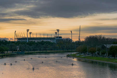 MELBOURNE, AUSTRALIA - 13 June 2020: Single scull rowers scattered on the Yarra River in front of the Melbourne Cricket Ground (MCG)