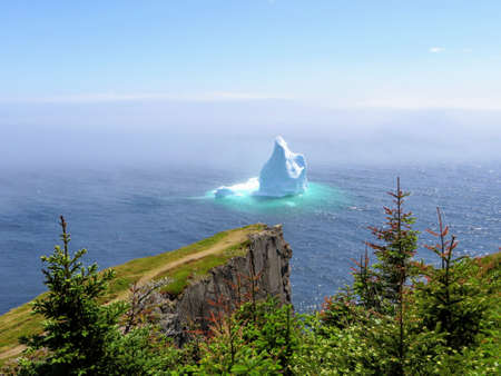 Incredible iceberg floating along the rugged coast beside the Skerwink Trail in Newfoundland and Labrador, Canada Stok Fotoğraf
